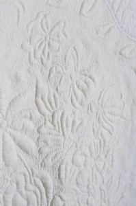 Detail on a white-on-white quilt with stippling